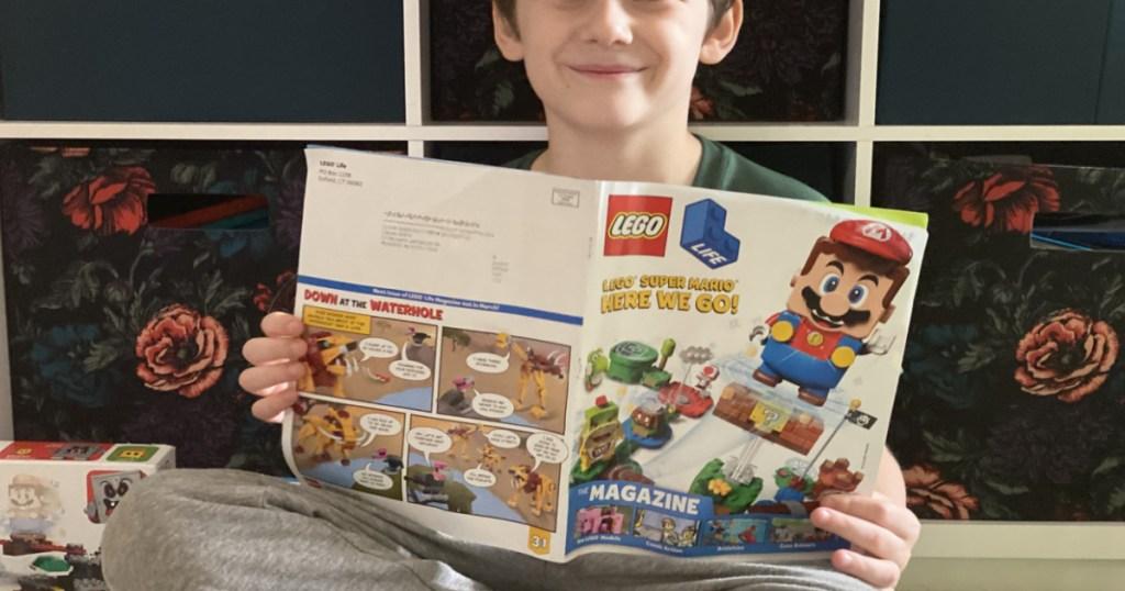 boy holding LEGO Life magazine