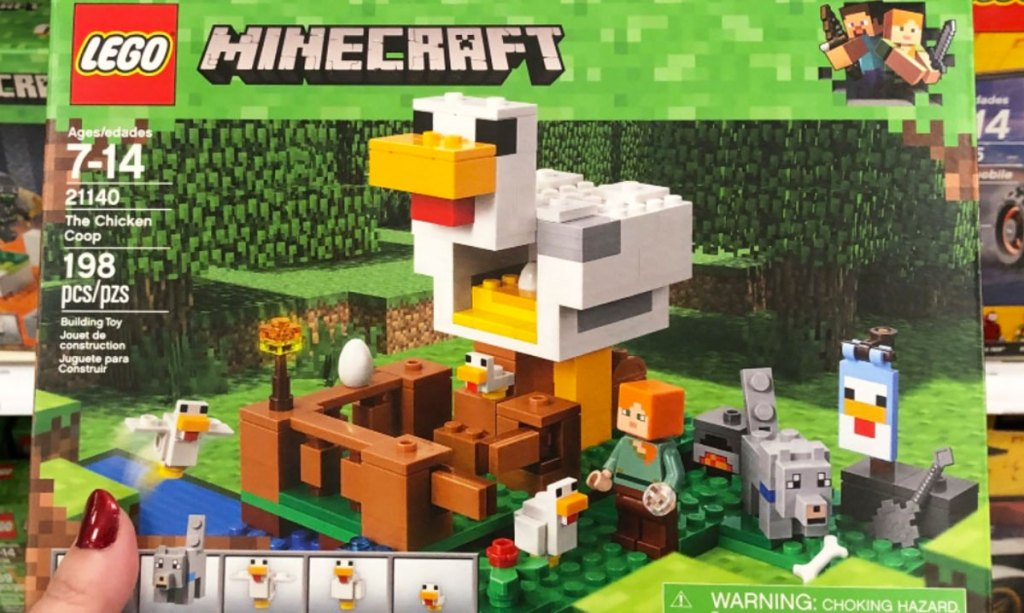 woman with red nails holding up LEGO minecraft chicken coop set in green box