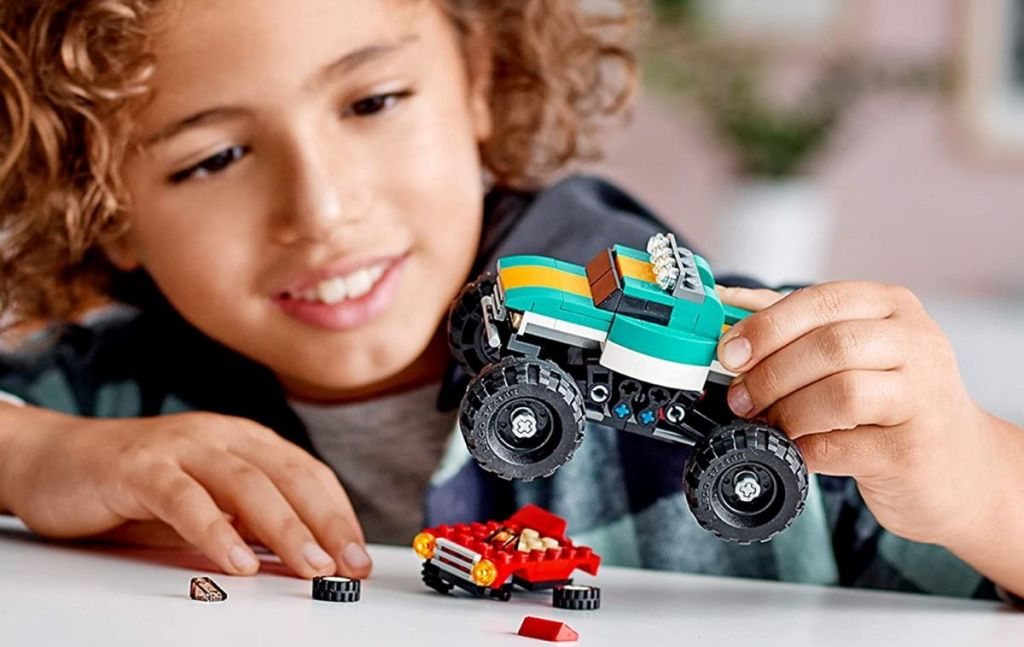boy playing with a LEGO monster truck