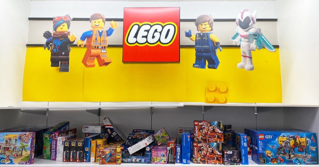 yellow lego sign with minifgiures above a shelf full of lego sets at kohl's