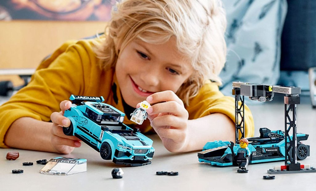 boy in yellow shirt laying on ground building a bright blue and black lego speed champions set