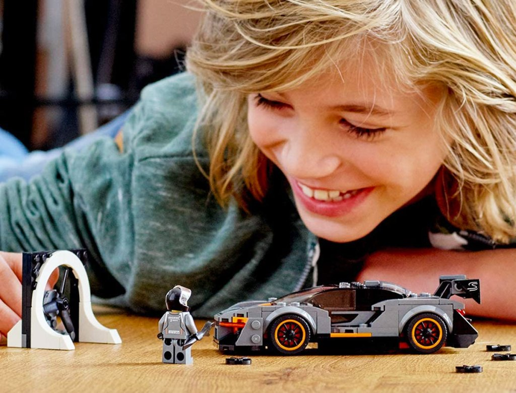 boy with blonde hair playing with a grey McLaren LEGO car