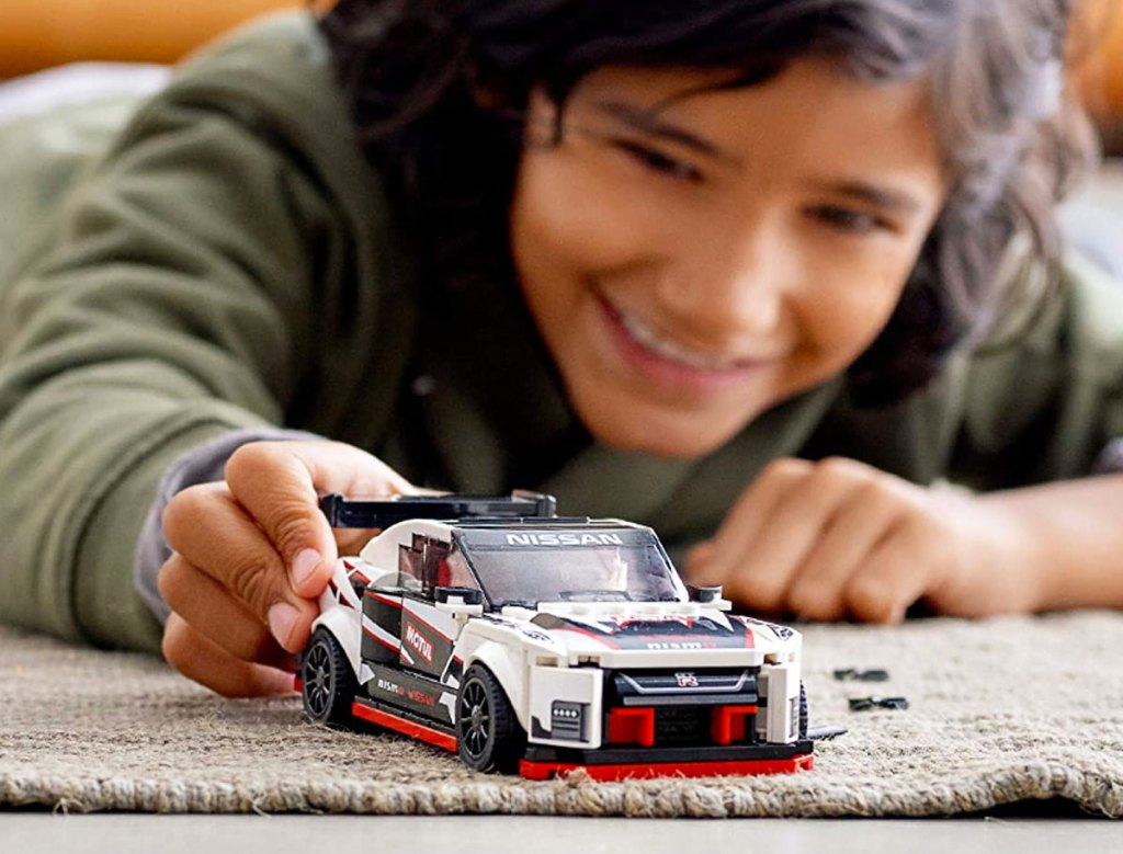 boy in green long sleeve shirt laying on ground playing with a white nissan lego car