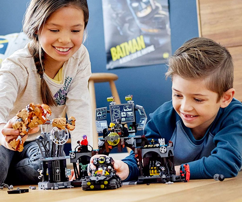 boy and girl playing with lego batcave set on floor