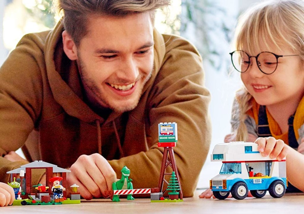 man and girl playing with lego toy story 4 RV set on wood floor