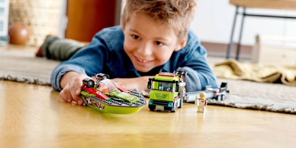 boy playing with LEGO boat transporter