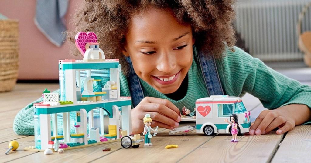 girl playing with LEGO heartlake city hospital