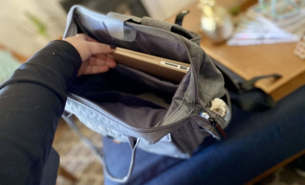 A hand placing a laptop in a bag