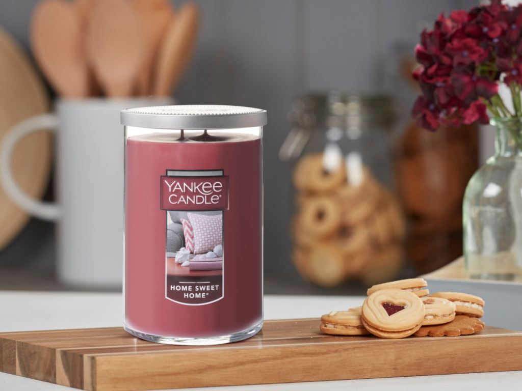large yankee candle in home sweet home next to cookies on a cutting board