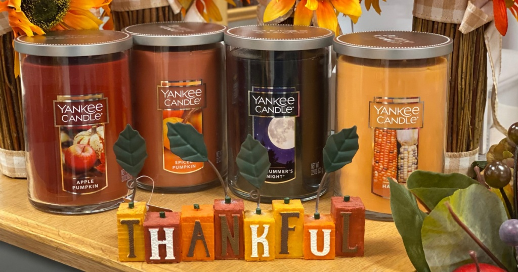 4 large yankee 2 wick sitting on a table behind a thankful sign