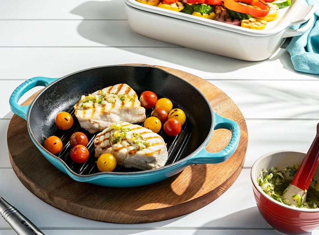 blue cast iron le creuset pan with grilled chicken inside