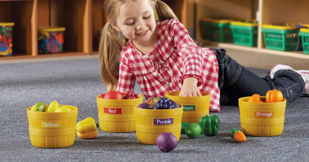 girl in red and white checkered shirt sitting on floor playing with plastic baskets of fruits and vegetables labeled by color