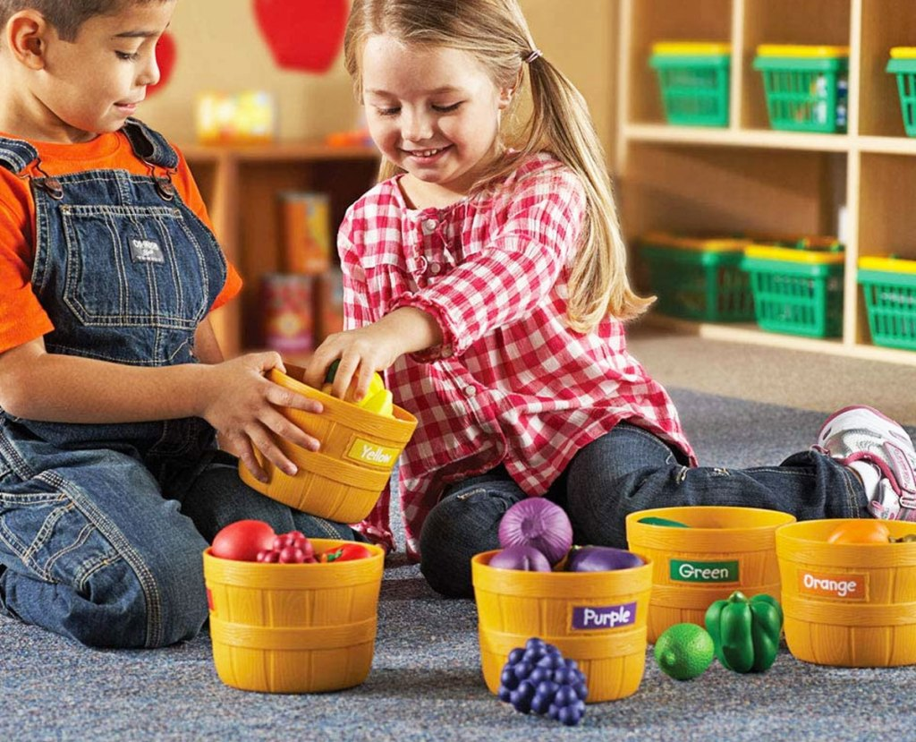 boy and girl sitting on floor playing with plastic baskets of fruit sorted into different colors