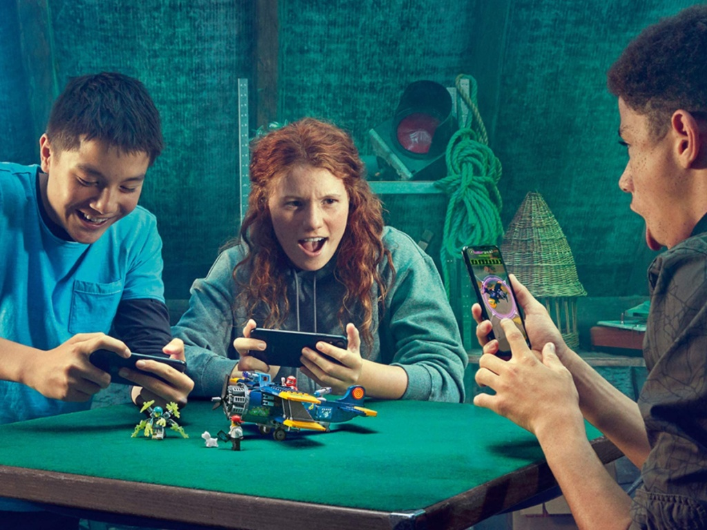 3 kids sitting around a table playing with a lego plane set