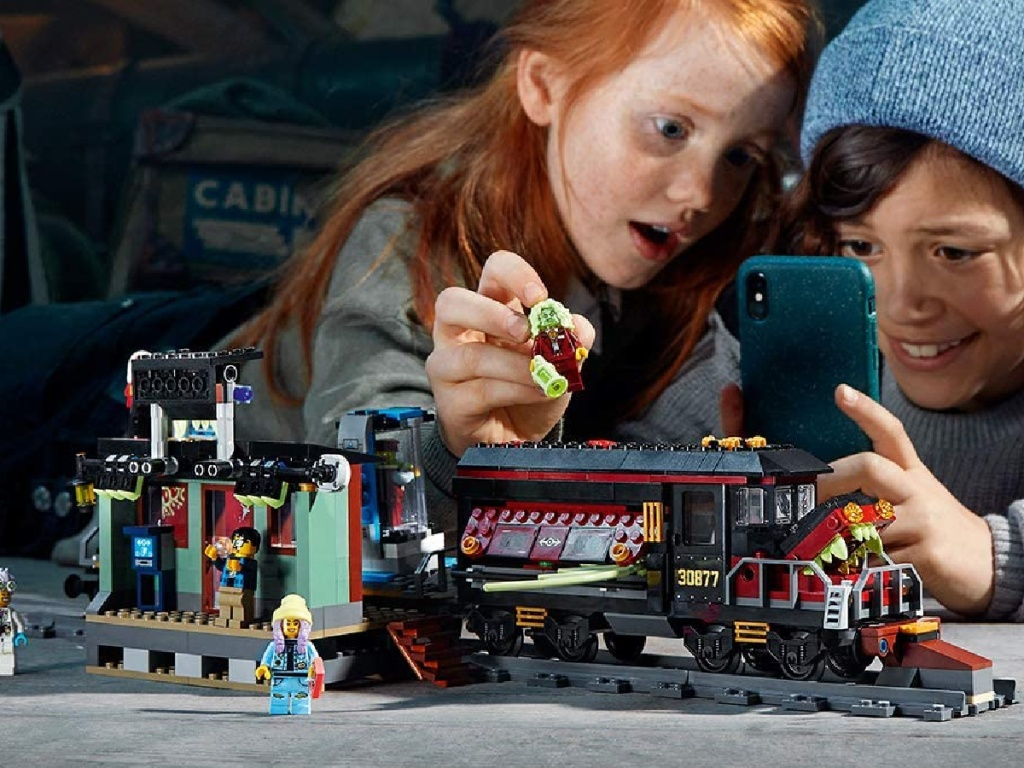 2 children playing with a lego hidden side train