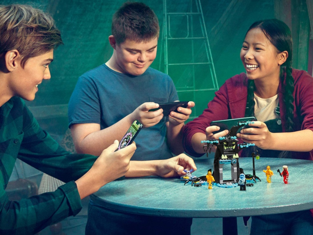3 kids standing around a table playing with a lego set