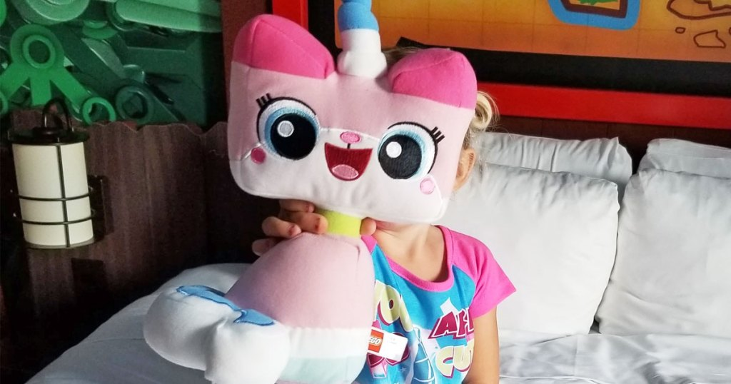 girl sitting on a bed holding up a pink lego movie unikitty plush