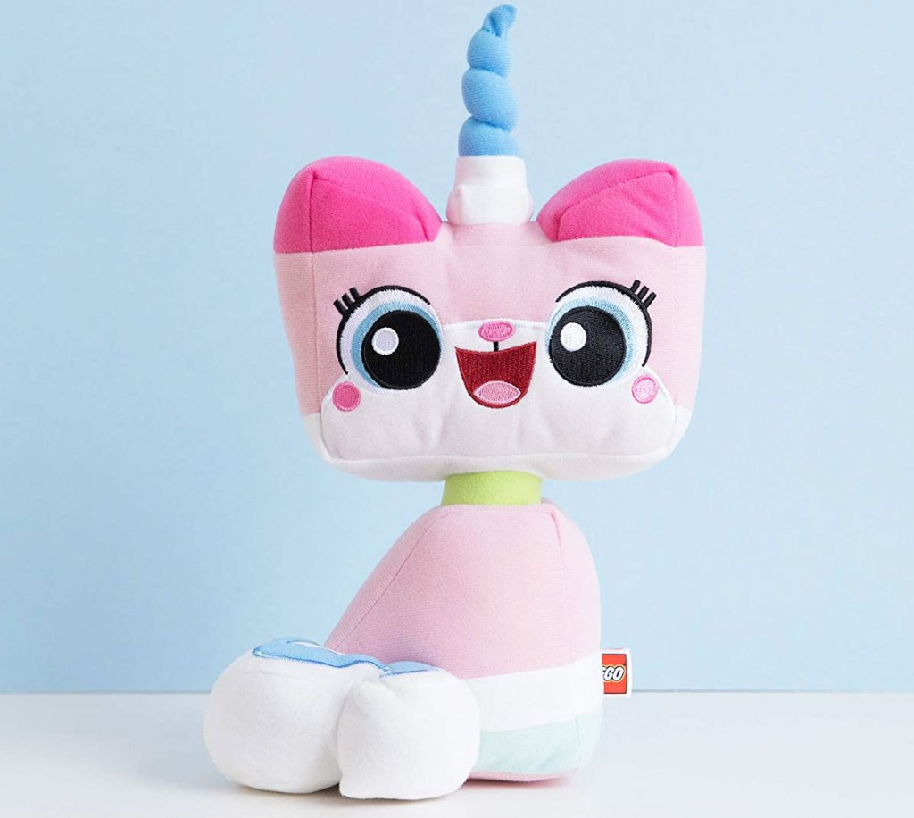 pink lego unikitty plush toy with blue unicorn horn sitting on a white table with blue background
