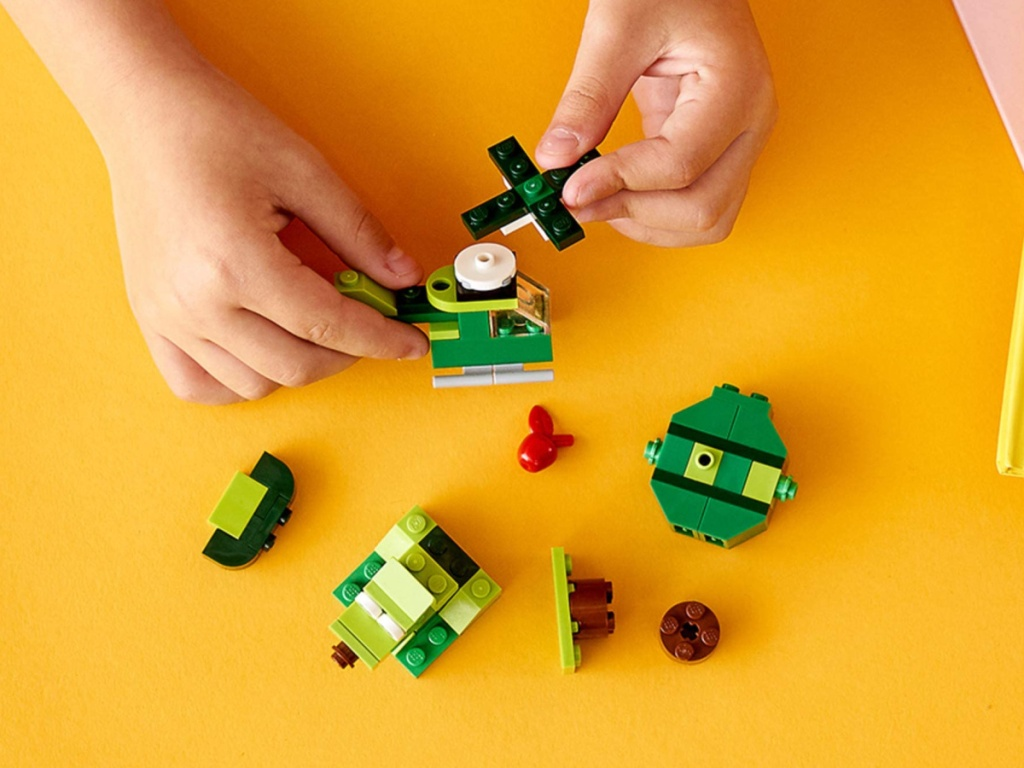 child playing with green lego set