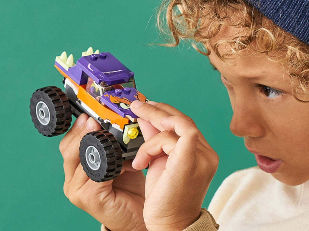 little boy playing with a lego monster truck set