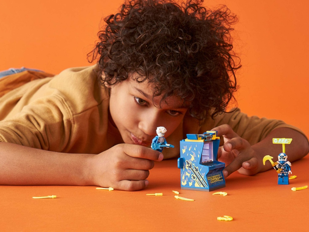 little boy laying on the floor playing with a lego ninjago play set