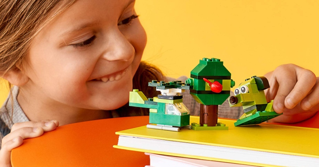 little girl playing with green lego set