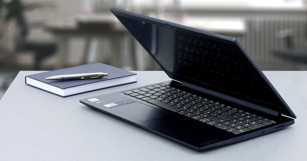 laptop, notebook, and pen on table