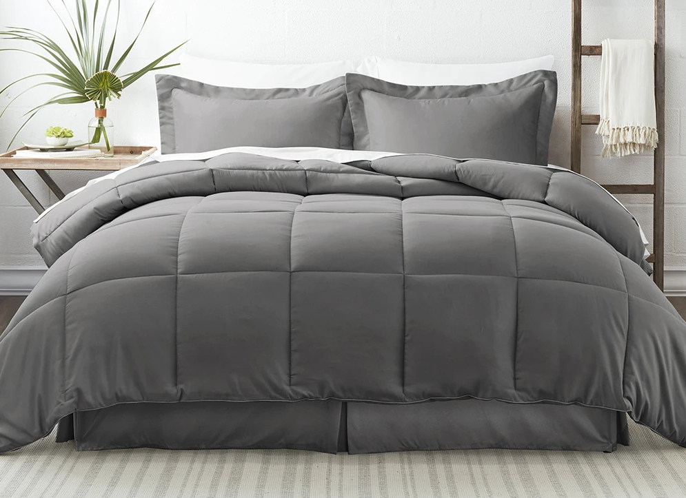 bed with gray blankets and pillows on it