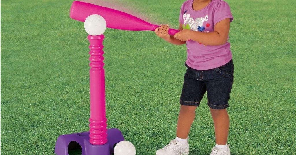 girl holding a t-ball bat