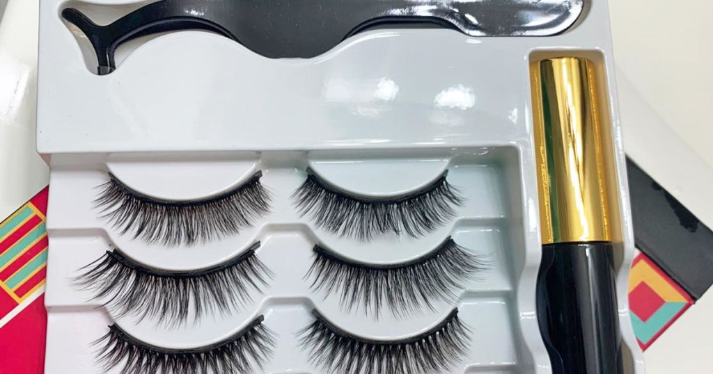 set of lashes, eyeliner, and applicator tool in a white tray