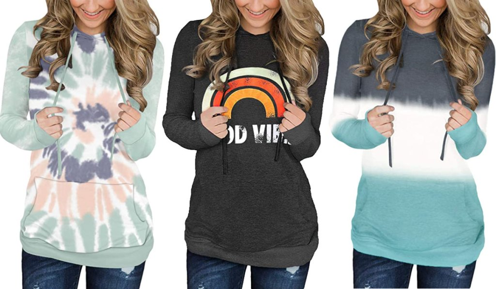 three women modeling pullover hoodies in light green and pink tie dye swirl, grey with rainbow that says good vibes, and grey, white, and light green color block