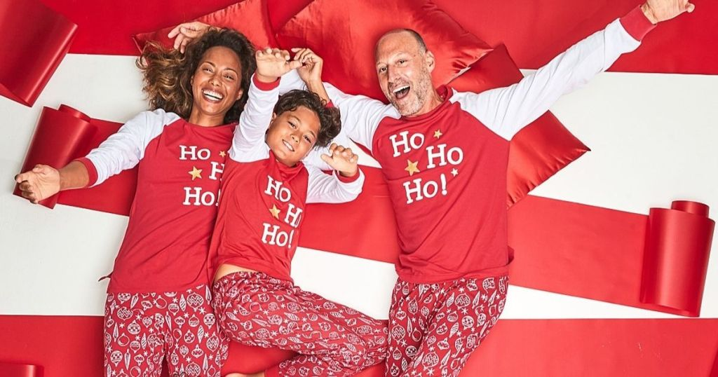 family laying on wrapping paper in matching pajamas