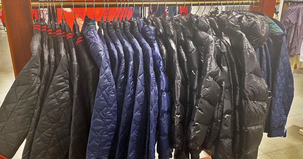 quilted and puffer jackets in black and blue colors on a display rack at macy's