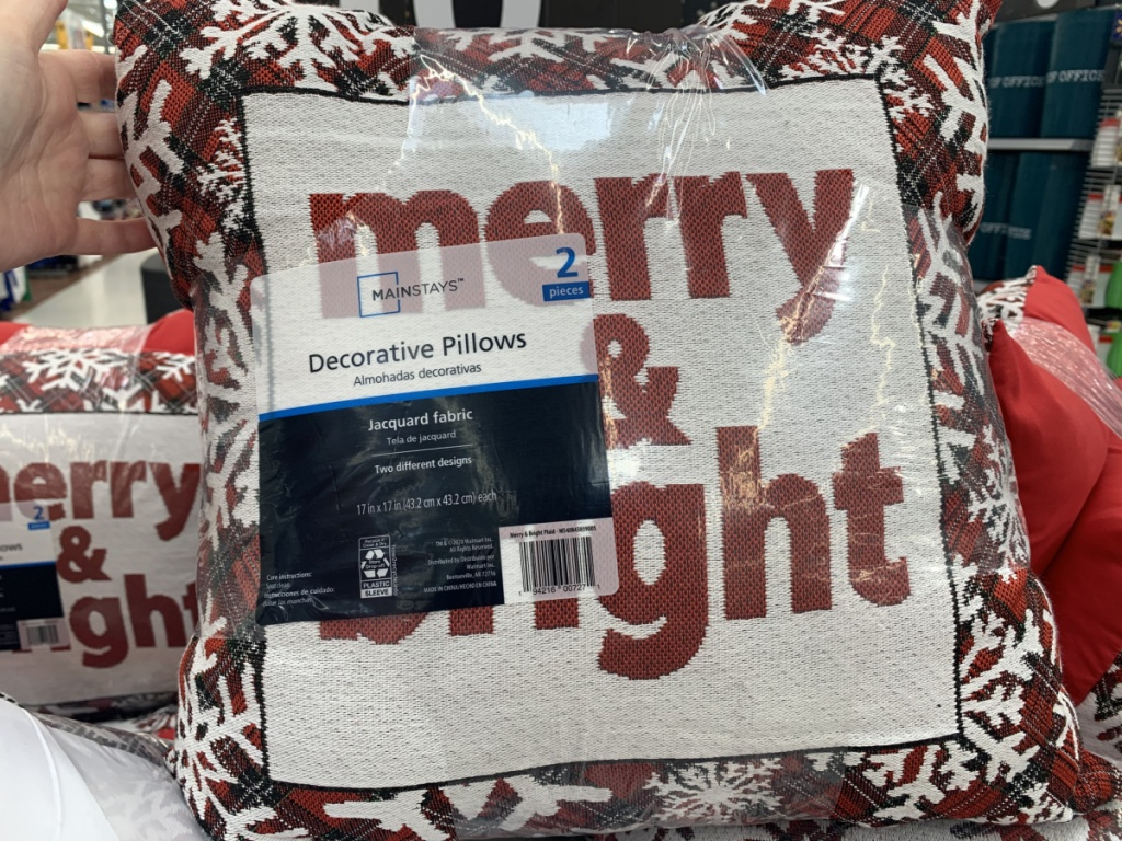 hand holding Christmas pillow set in store