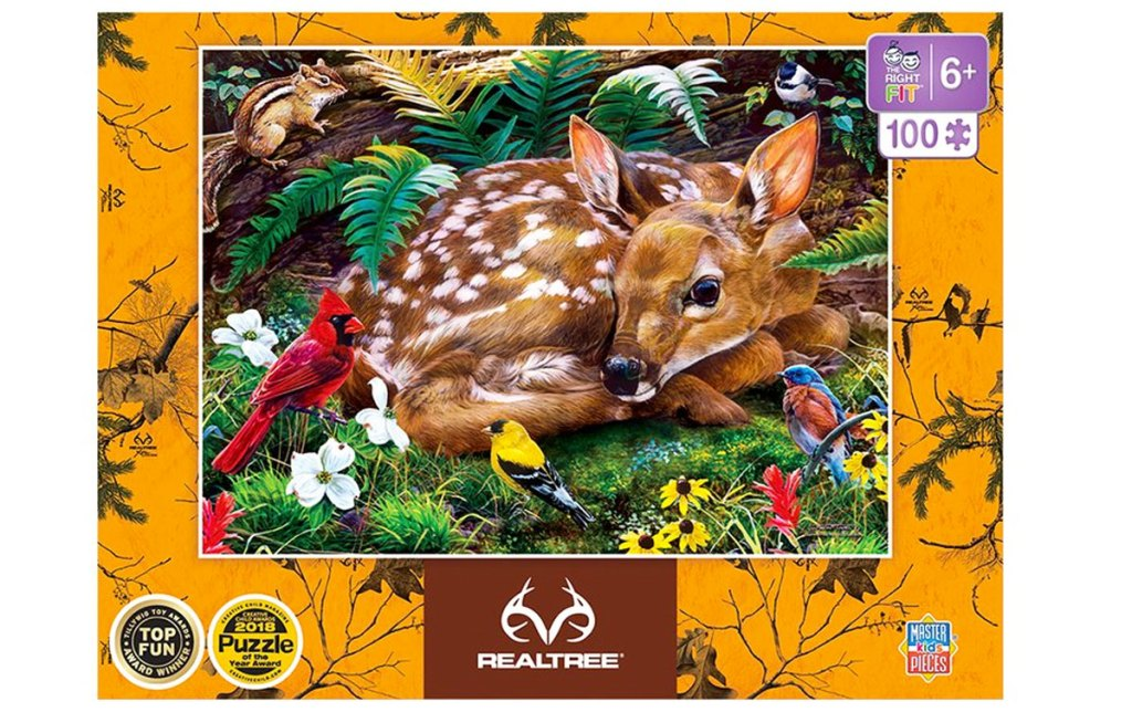 box for a puzzle of a deer fawn curled up in grass with colorful birds around it