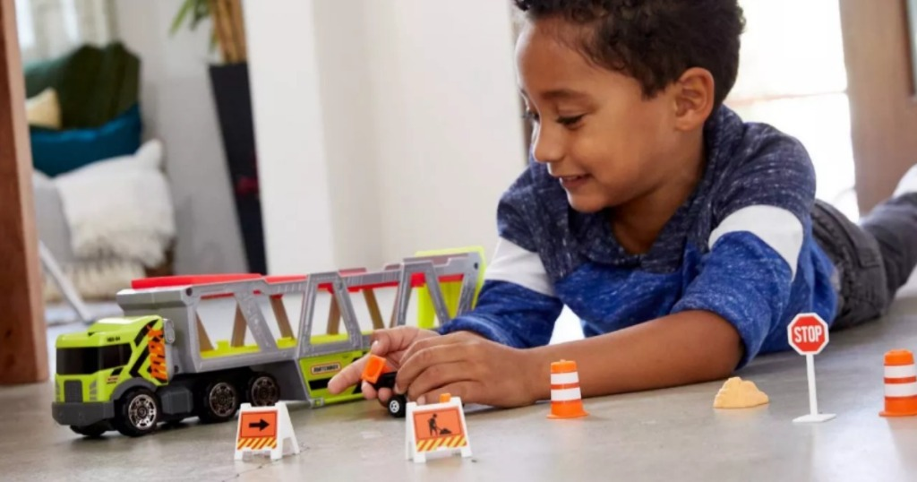 boy playing on floor with Matchbox Construction Hauler