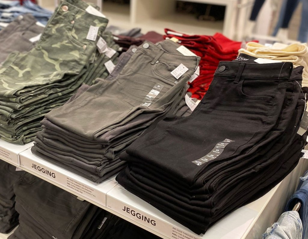 white display table with pairs of folded women's jeggings in black, grey, and camo print