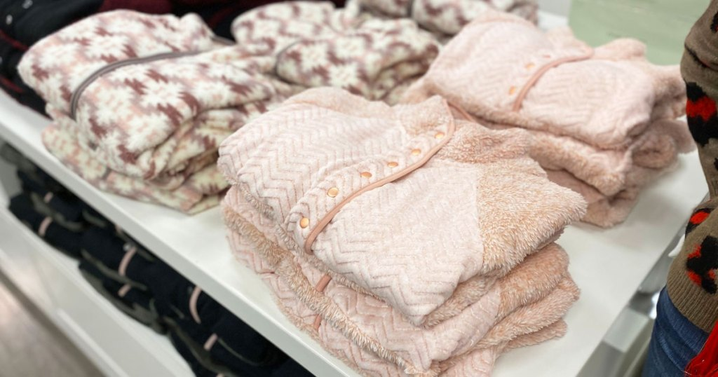 stacks of light pink sherpa sweatshirts folded on a white display table