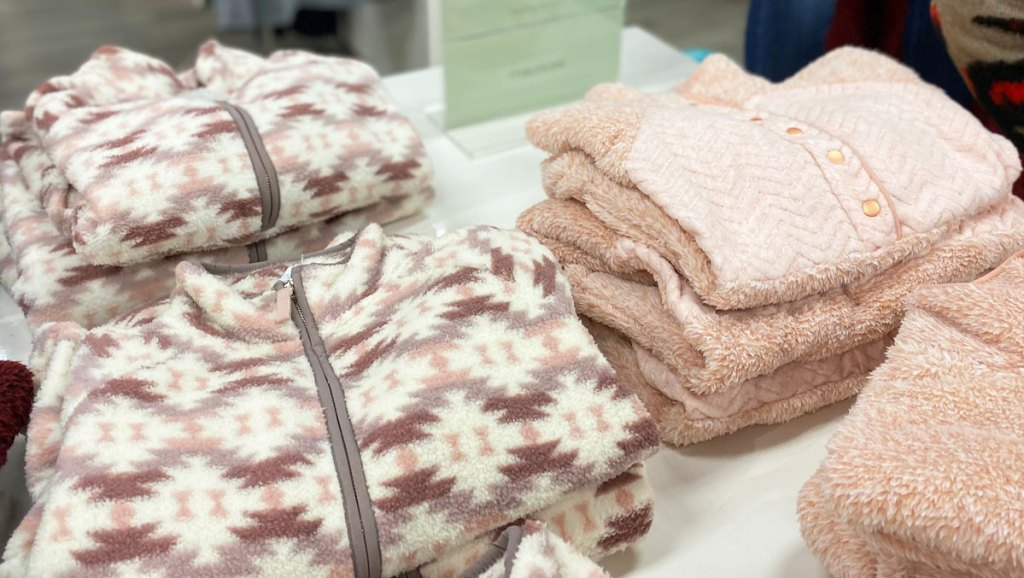 white and pink aztec print and solid light pink sherpa sweatshirts folded on display table