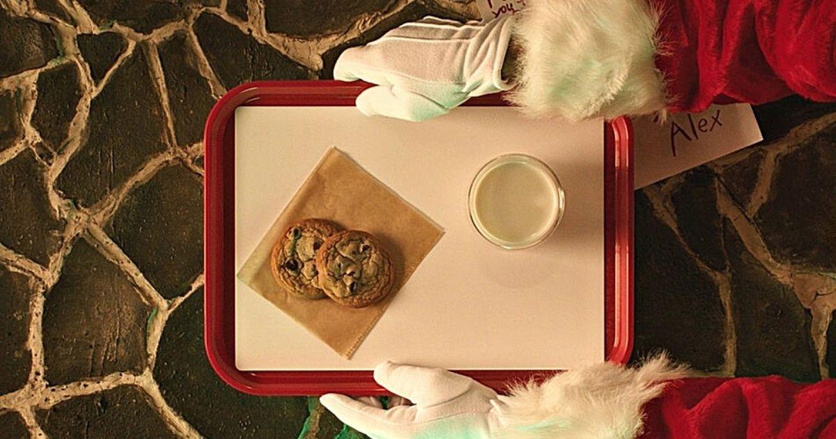 tangan yang memakai sarung tangan Santa memegang nampan dengan kue chocolate chip