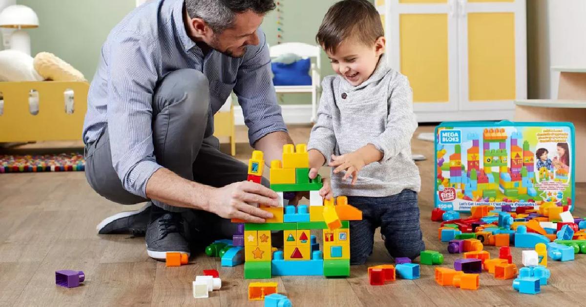 pria dan anak laki-laki di lantai bermain dengan balok bangunan berwarna-warni