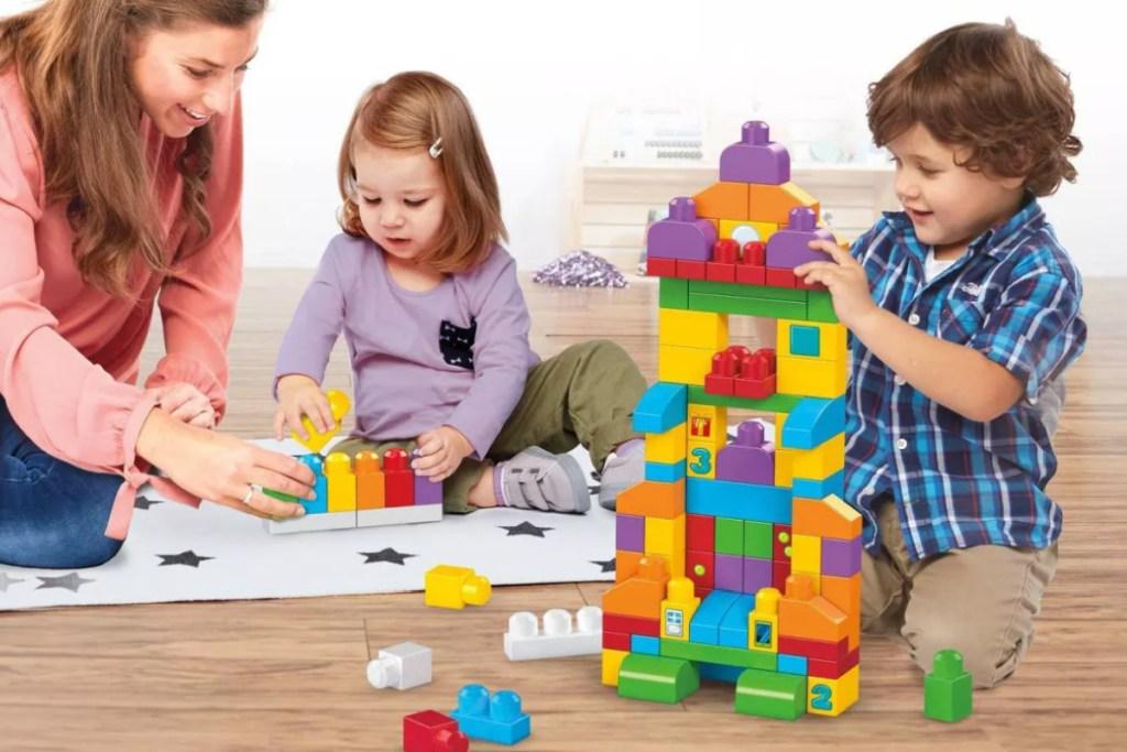 Wanita dan dua anak duduk di lantai bermain dengan balok bangunan berwarna-warni