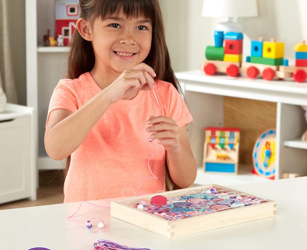 girl playing with Melissa Doug Beads Set