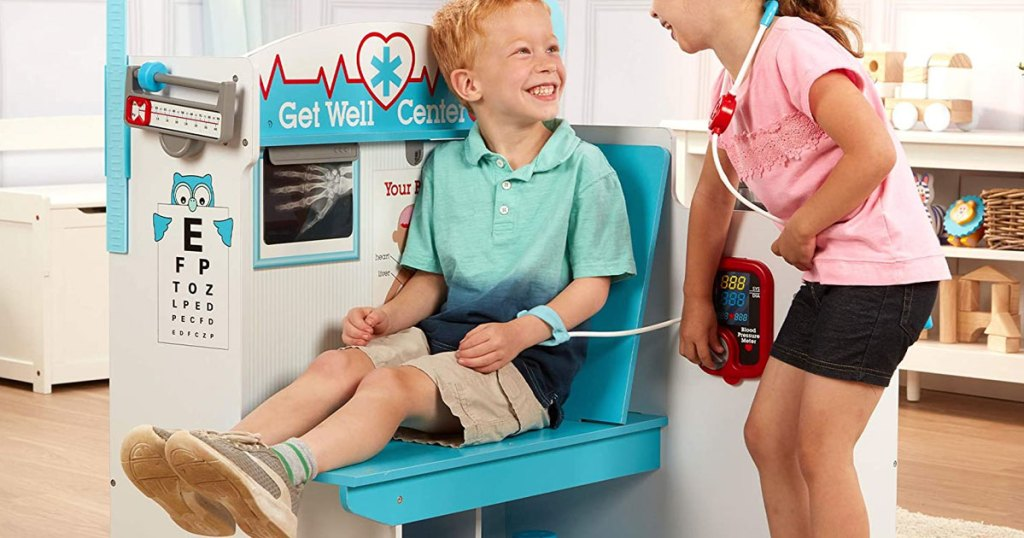 boy and girl playing with a large wood doctor office playset