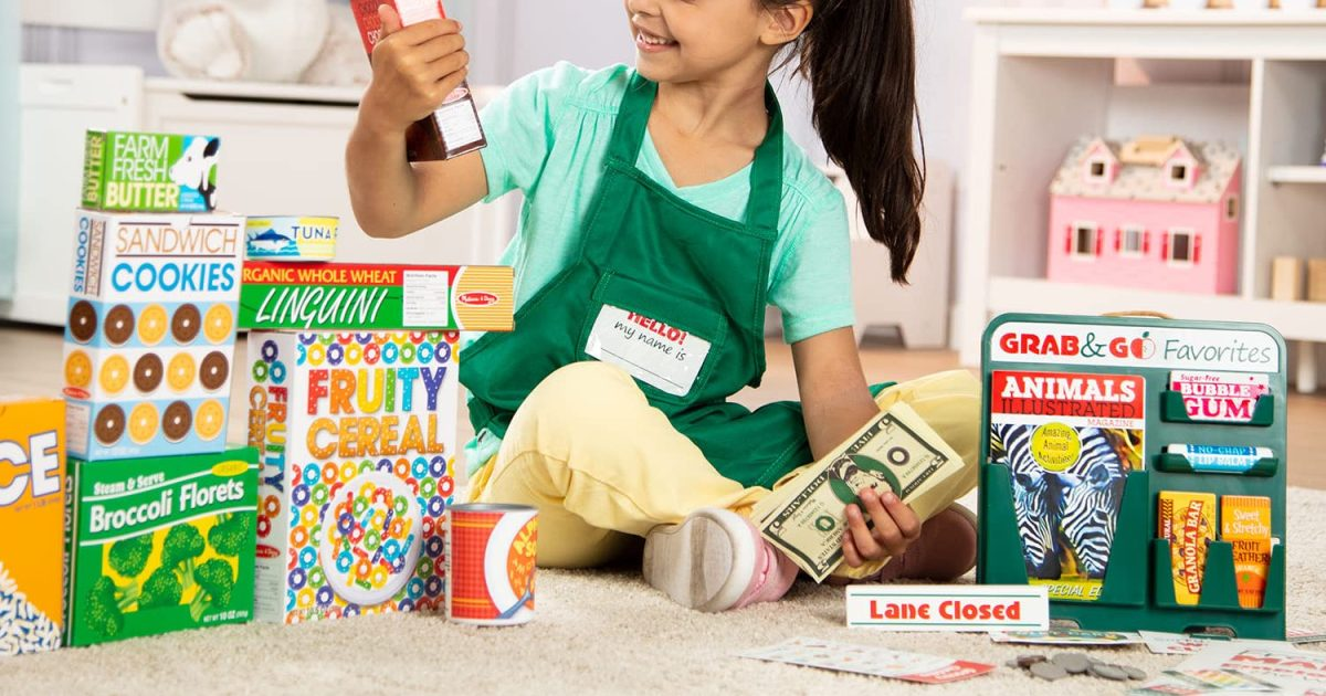 girl on floor playing with grocery store toys