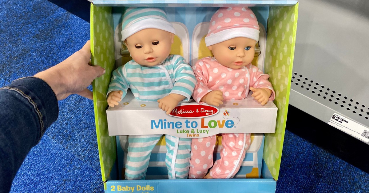 Hand holding a two pack of baby dolls