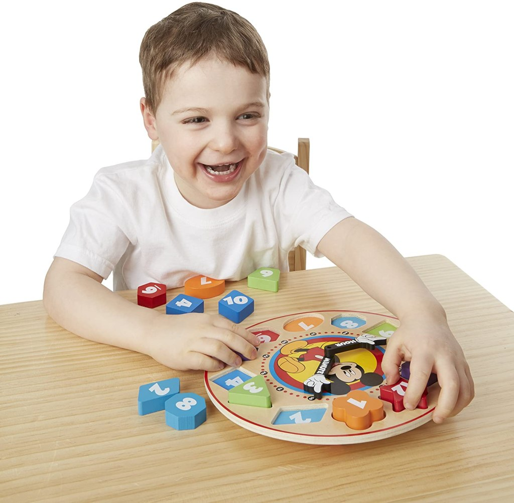 boy playing with Melissa Doug Mickey Clock