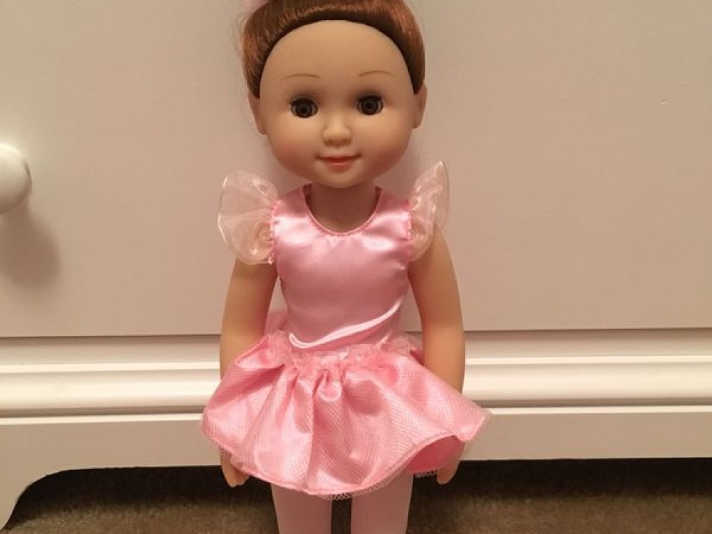 ballerina doll standing against white dresser