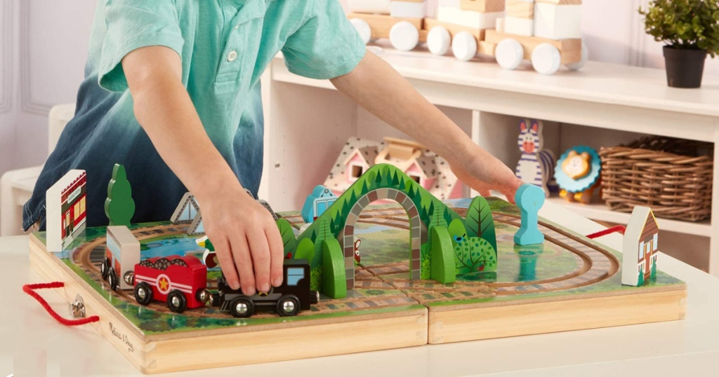 little boy playing with melissa and doug wooden train set