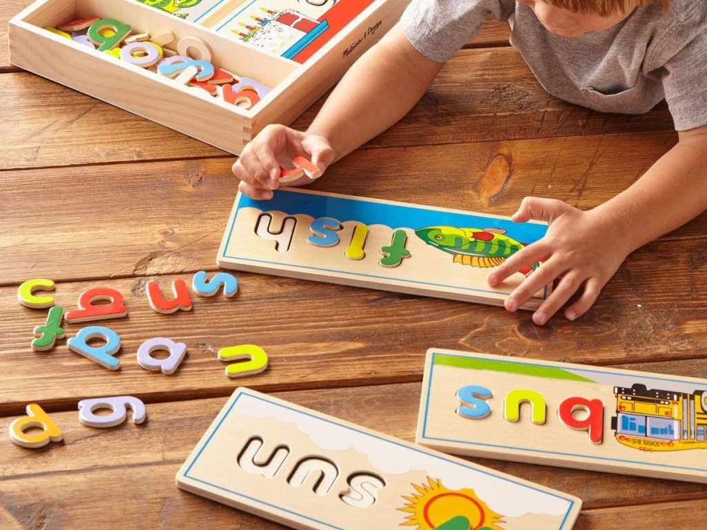 small child layng on a wood floor playing with a melissa and doug wooden letter set